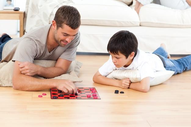 Uomo bello che gioca a dama con suo figlio sdraiato sul pavimento