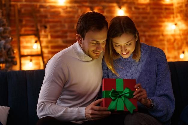 Uomo bello che presenta un regalo alla sua bella moglie e sorridente
