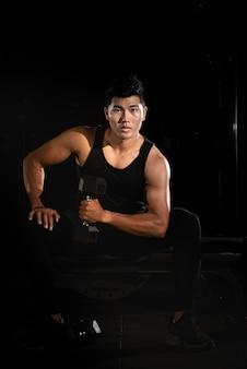 Uomo bello che alza il dumbbell, facendo esercizio per il muscolo del buit, corpo adatto e fermo, posa di modello