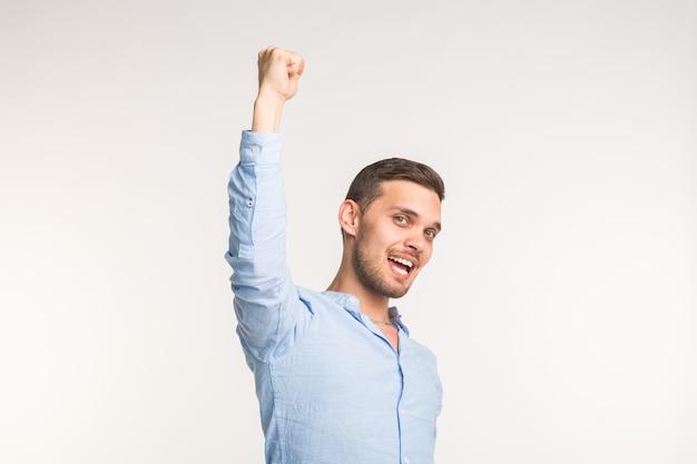 Uomo bello alzando una mano sopra la testa sul muro bianco
