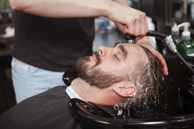 Bell'uomo rilassato in un barbiere