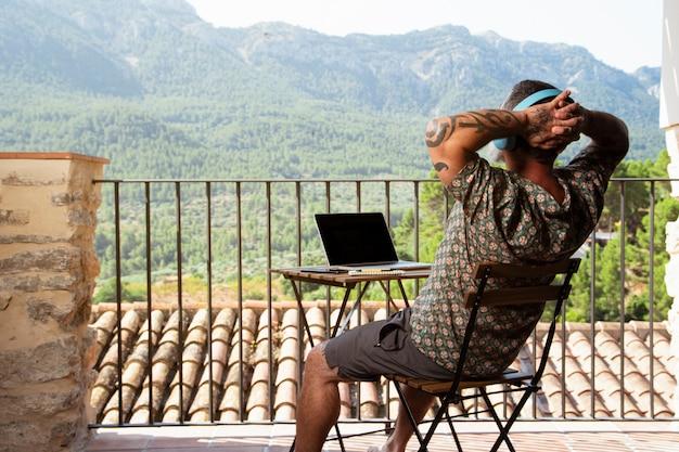 Bell'uomo rilassarsi e lavorare su un laptop sul balcone di casa sua, mentre si ascolta la musica e si gode la vista sulle montagne