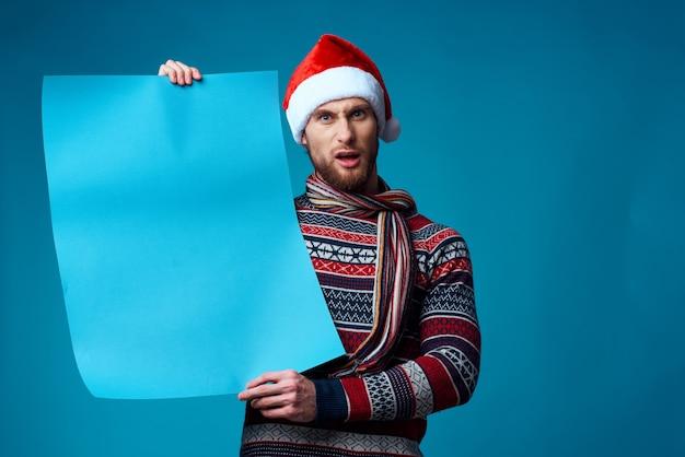 Bell'uomo con un cappello da babbo natale che tiene in mano uno striscione vacanza sfondo blu