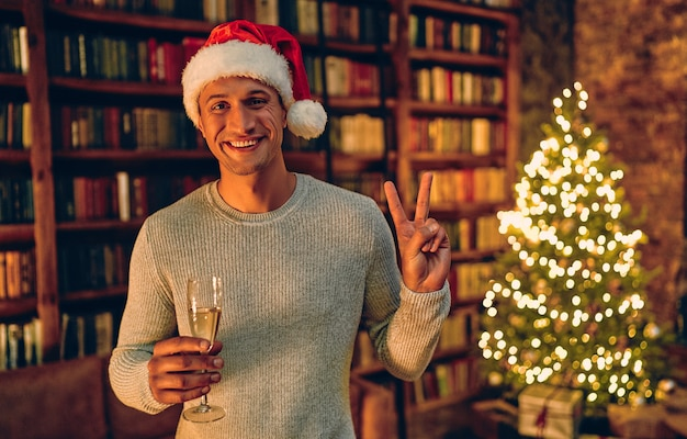 Bell'uomo in santa cappello con un bicchiere di champagne. sullo sfondo di un albero di natale con doni. felice anno nuovo e buon natale!