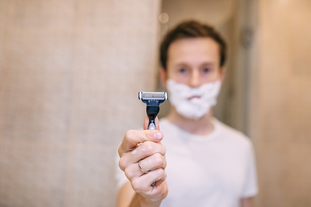 Uomo bello in schiuma da barba con il rasoio, in bagno