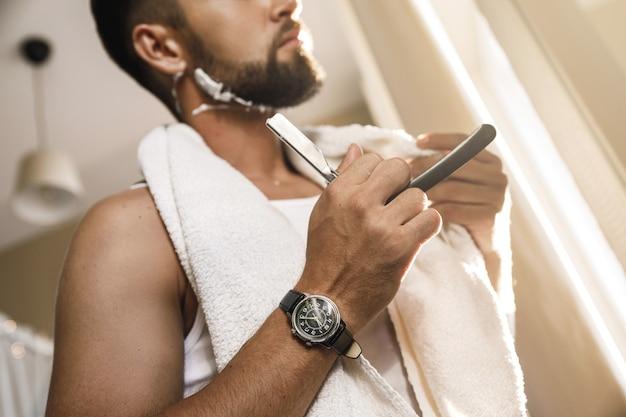 Uomo bello che rade la barba con un rasoio a mano libera