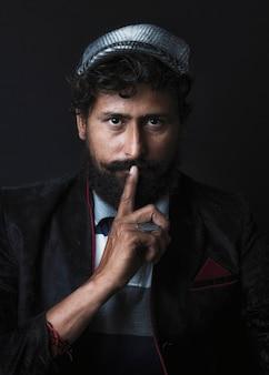 Uomo bello che mostra gesto di silenzio con il dito sulle labbra