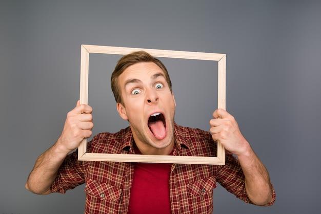 Uomo bello che mostra la lingua e tenendo il telaio in legno
