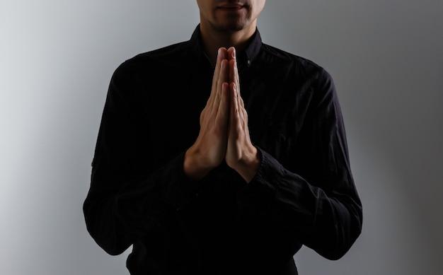 Bell'uomo sedersi preghiera su sfondo nero. le sue mani stanno pregando per le benedizioni di dio.