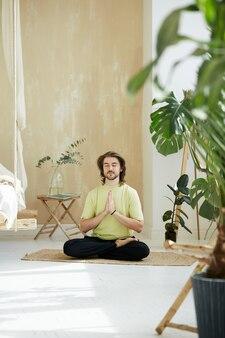 Uomo bello che si siede nella posa del loto che tiene le braccia in namaste, insegnante di meditazione che pratica la concentrazione a casa con piante verdi