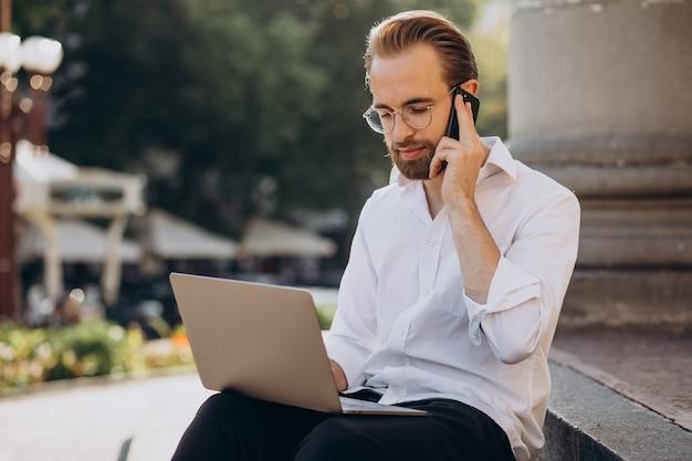 Bell'uomo seduto sulle scale e lavorando al computer