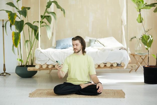 Uomo bello che si siede sul materassino yoga utilizzando il telefono, insegnante di yoga a casa tenendo il telefono per la lezione online