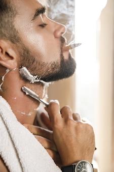 Uomo bello che fuma una sigaretta e si rade la barba con un rasoio a mano libera