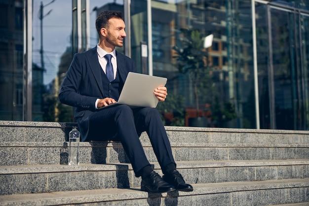 Bell'uomo che trascorre del tempo fuori dal centro affari sulle scale mentre lavora online sul laptop