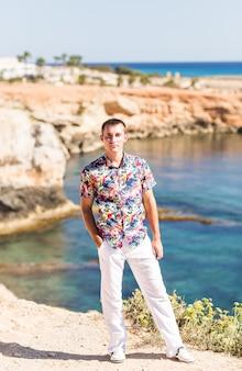 Uomo bello che sta sulla spiaggia