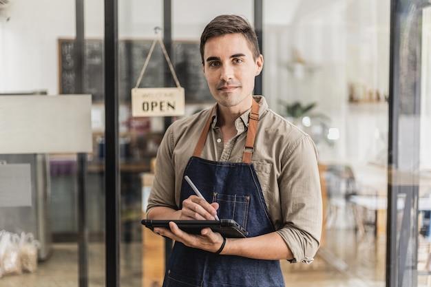 Bell'uomo in piedi con in mano un tablet e prende appunti, fa il commesso, indossa un grembiule e serve i clienti che vengono a usufruire del servizio al bar. concetto di servizio di caffè.