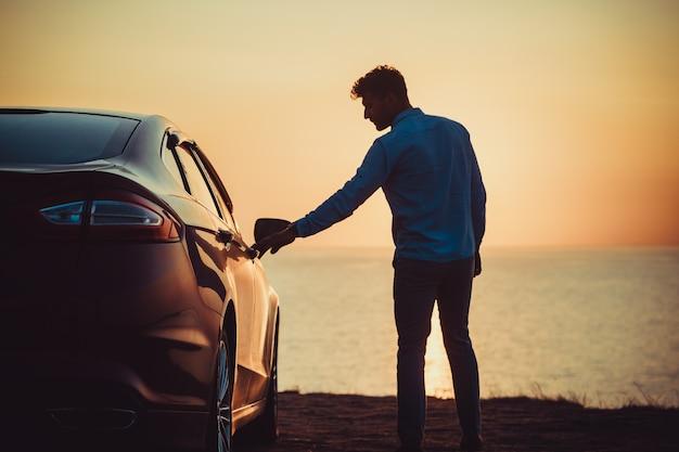 Il bell'uomo in piedi vicino alla macchina in riva al mare