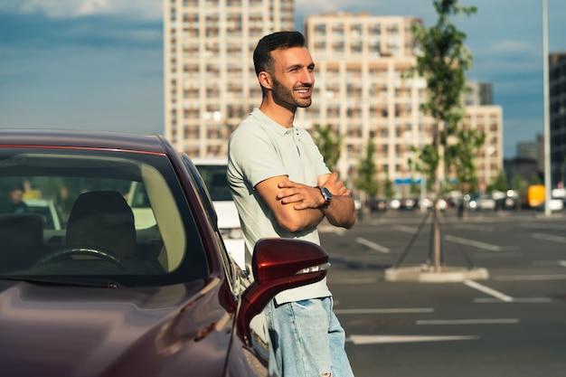 Il bell'uomo sta vicino alla macchina nuova nel parcheggio