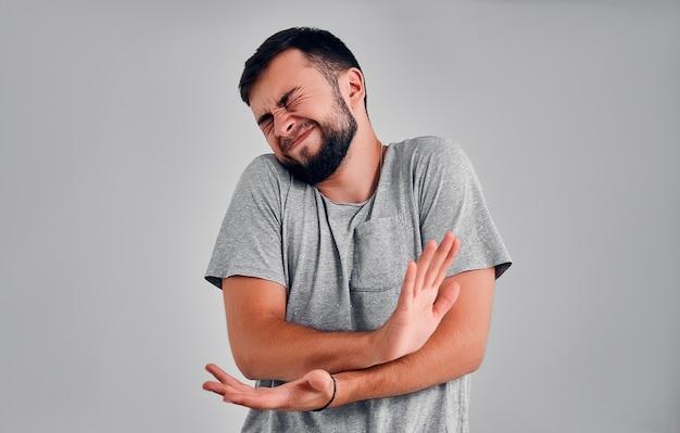 Uomo bello che soffre di dolore su sfondo grigio concetto di dolore