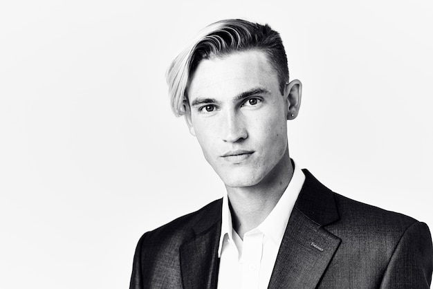 Un bell'uomo in giacca e cravatta tiene la mano vicino al viso acconciatura alla moda foto in bianco e nero