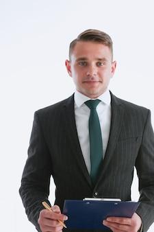 Uomo bello in giacca e cravatta guardando direttamente le mani incrociate sul petto isolato sullo sfondo.