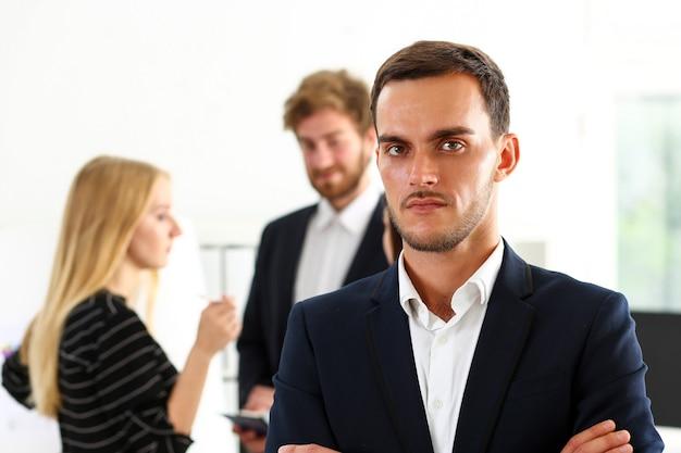 Uomo bello in giacca e cravatta guardando direttamente con le mani incrociate sul petto isolato sfondo.