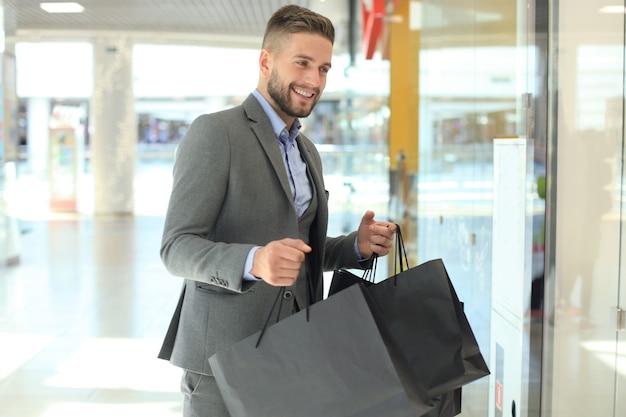Bell'uomo vestito con borse della spesa.