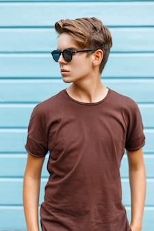 Uomo bello in occhiali da sole in piedi vicino alla parete di legno blu.