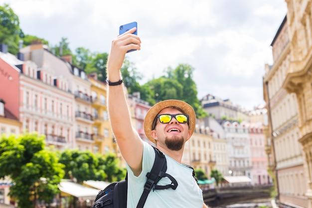 Uomo bello che cattura selfie con la fotocamera del cellulare smart in città europea.
