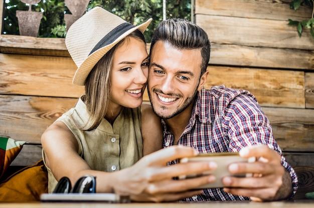 Uomo bello che cattura selfie con bella donna al bar di moda