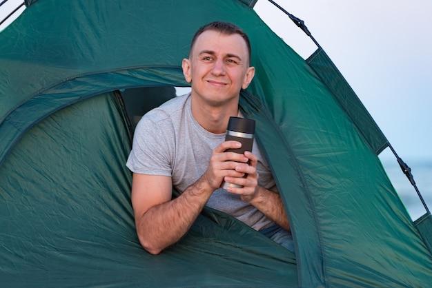 Uomo bello in una tenda turistica che tiene tazza termica