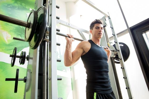 Bell'uomo che si allena in palestra per rimanere in forma e forte