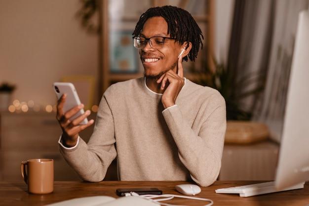 Uomo bello che utilizza il suo smartphone a casa con gli auricolari