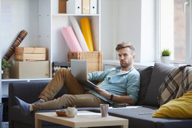 Uomo bello che per mezzo del computer portatile sul sofà