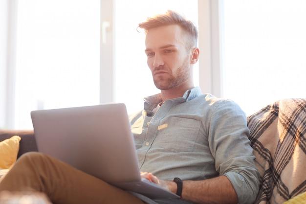 Uomo bello che utilizza computer portatile al sole
