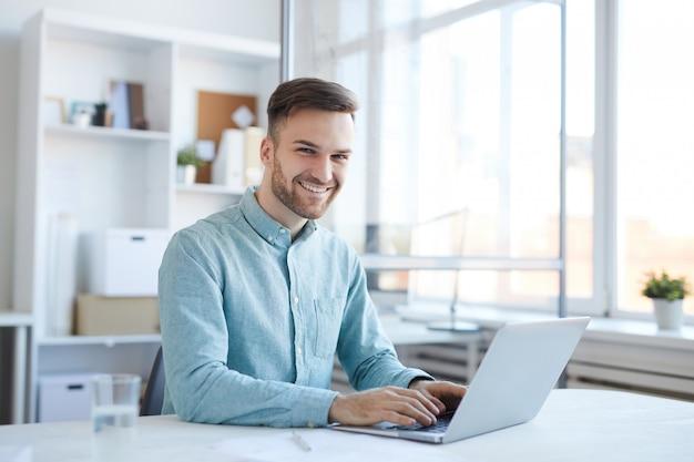 Uomo bello che per mezzo del computer portatile