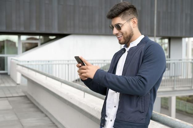 Bell'uomo che utilizza l'app del telefono cellulare che invia messaggi fuori dall'ufficio in una città urbana con grattacieli che costruiscono...