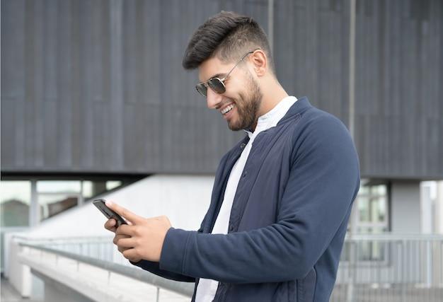 Bell'uomo che utilizza l'app del telefono cellulare che invia messaggi al di fuori dell'ufficio in una città urbana con grattacieli che costruiscono...