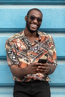 Bell'uomo che utilizza uno smartphone moderno all'aperto