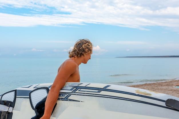 Camminata bella dell'uomo con la tavola da surf in bianco bianca aspetta l'onda per navigare spot sulla riva dell'oceano del mare. concetto di sport, fitness, libertà, felicità, nuova vita moderna, vita bassa.