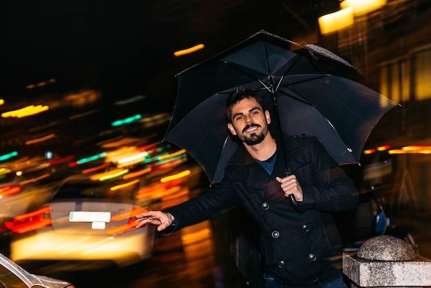 Bell'uomo che cammina a madrid di notte sotto la pioggia.
