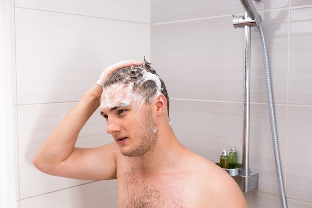 Bell'uomo che si lava i capelli gocciolanti e schiuma nella cabina doccia nel moderno bagno piastrellato