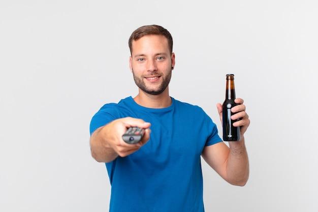 Bell'uomo che guarda la tv con una birra