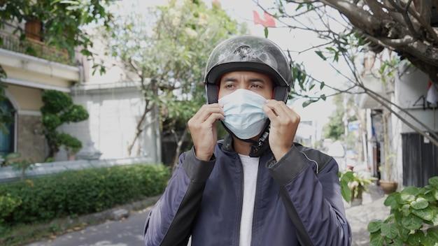 Un bell'uomo indossa una maschera mentre guida il suo scooter in moto