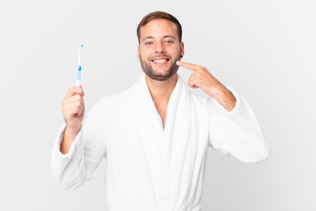 Bell'uomo che indossa accappatoio e tiene in mano uno spazzolino da denti