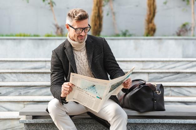 Bell'uomo che indossa un cappotto seduto all'aperto, leggendo un giornale
