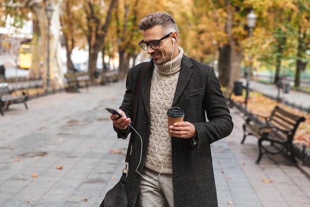 Uomo bello che indossa un cappotto che cammina all'aperto, ascoltando musica con auricolari e telefono cellulare, tenendo la tazza di caffè da asporto
