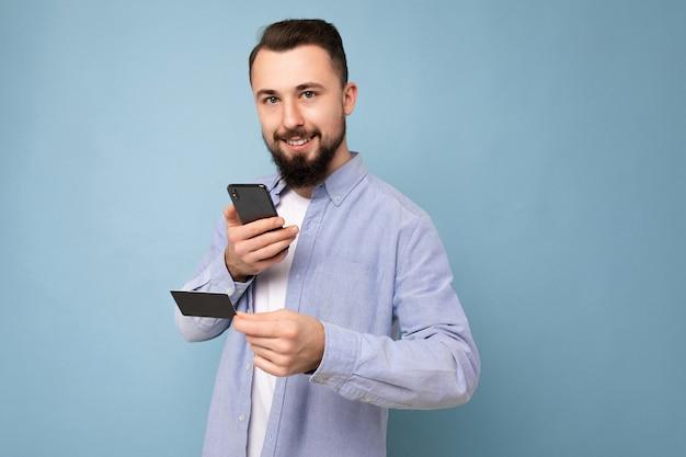 Bell'uomo che indossa abiti di tutti i giorni isolati sulla parete di fondo che tiene e utilizza il telefono e la carta di credito che effettuano il pagamento guardando la fotocamera.