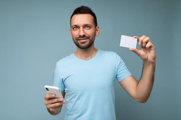 Uomo bello che indossa abiti di tutti i giorni isolati sulla holding della parete e utilizzando il telefono e la carta di credito per effettuare il pagamento guardando la fotocamera.