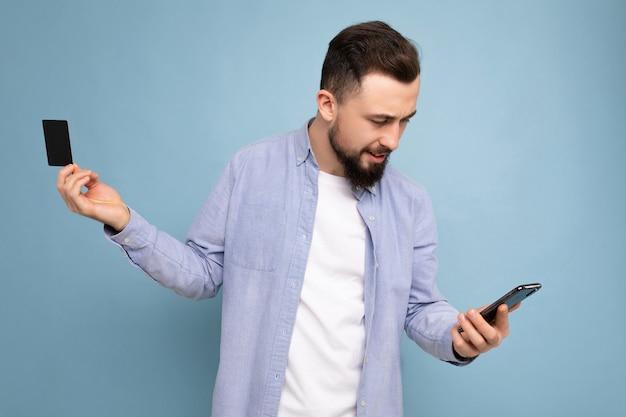 Uomo bello che indossa abiti di tutti i giorni isolati sulla holding della parete e utilizzando il telefono e la carta di credito che effettua il pagamento guardando lo schermo dello smartphone
